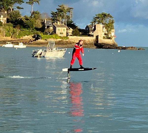 Mann schwebt mit E–Foil Board über das Wasser